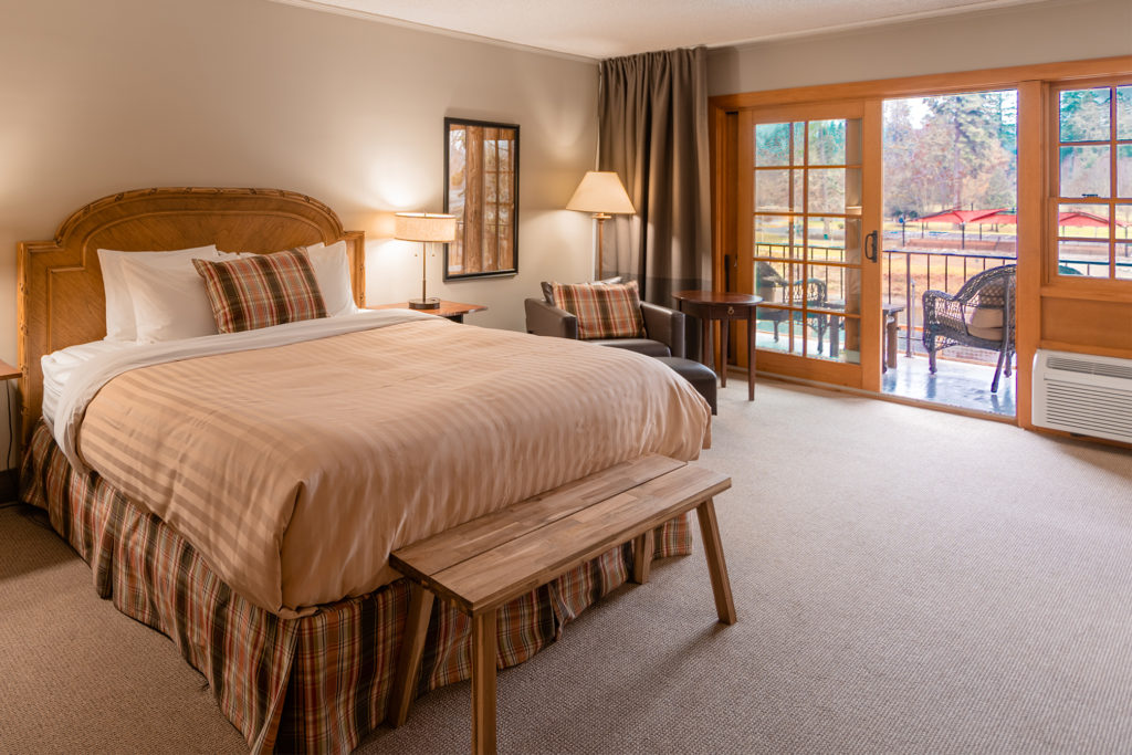 The deluxe king room with a king bed, bench footboard, chair, ottoman side table and wood trimmed sliding glass door to the balcony overlooking the Rogue River and Riverside Park across the river