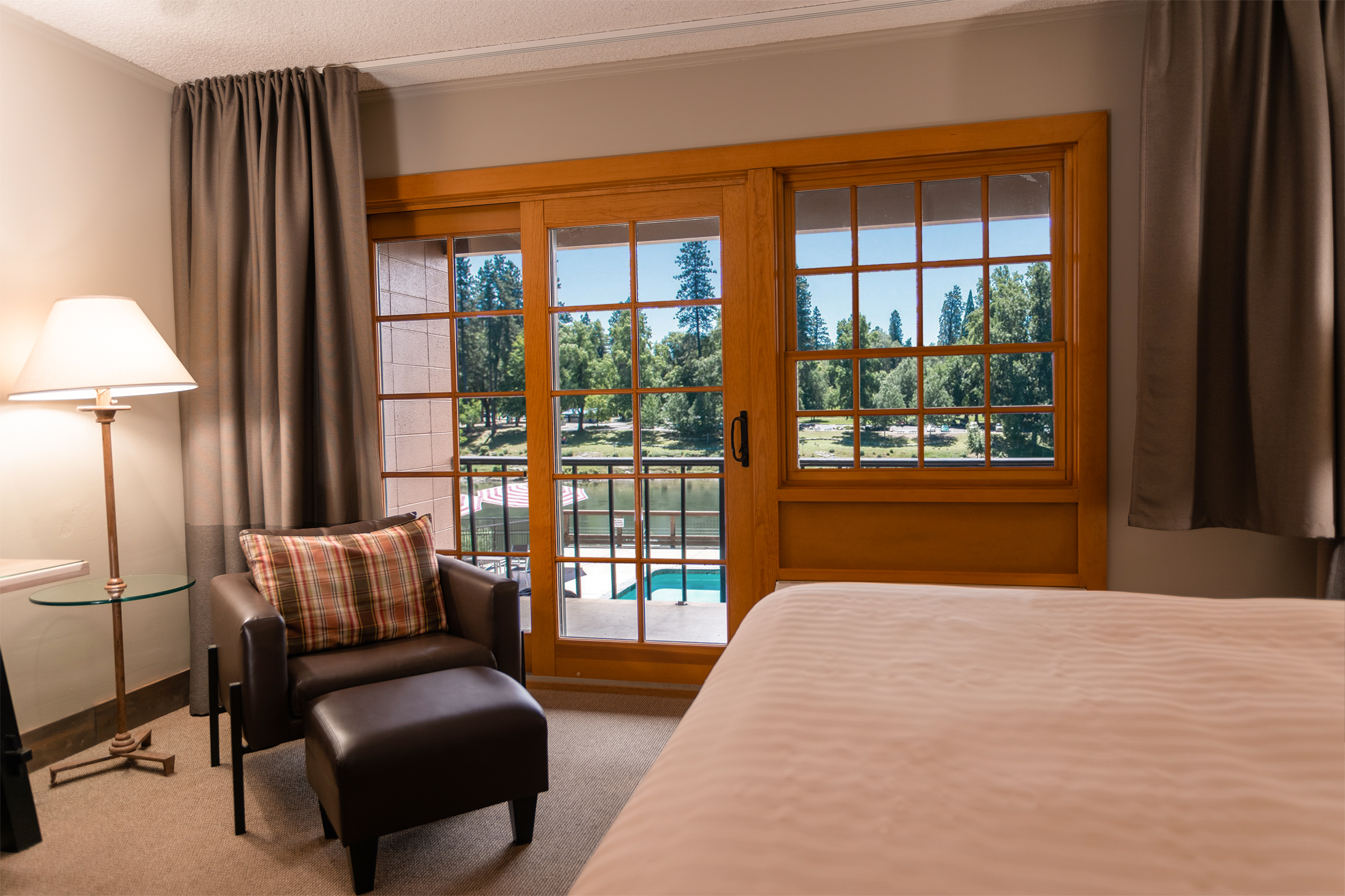 The Jr King bed leather chair and ottoman, and private balcony overlooking the Rogue River and Riverside Park in the distance