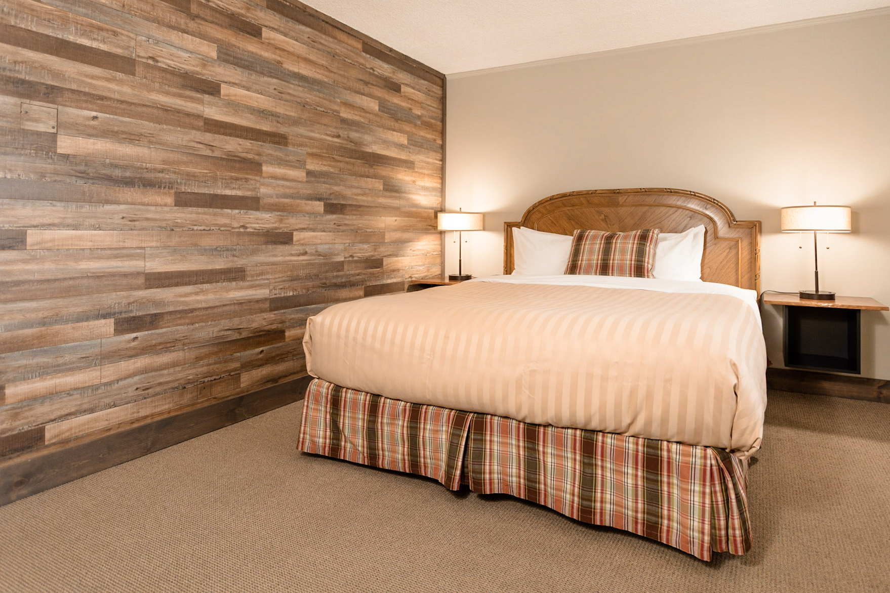 A standard king room with a wood pattern accent wall, bedside tables, lamps and 5 pillows